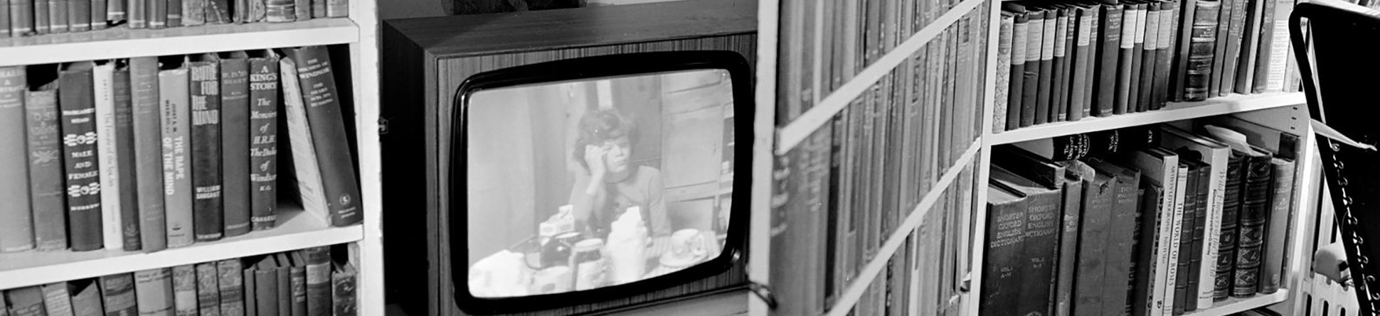 Black and white photo of a television in a bookcase