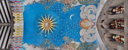 Church ceiling mural featuring sun, moon, stars, trees and a hand flanked by clouds, all against a bright blue background.