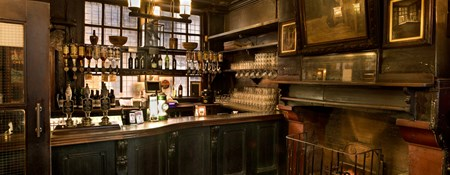 An interior detail of a bar area and fire place within a historic London public house.