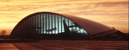 View of hangar at sunset with silhouettes of aircraft inside the building