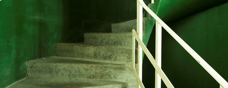 View of internal curved concrete stairs with distinctive emerald green walls at Saltdean Lido, West Sussex