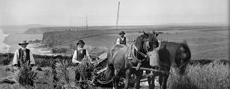 Black and white archive photograph of three farm workers and a horse drawn vehicle posing for the camera in a field, with radio masts, cliffs and coasts in the background.